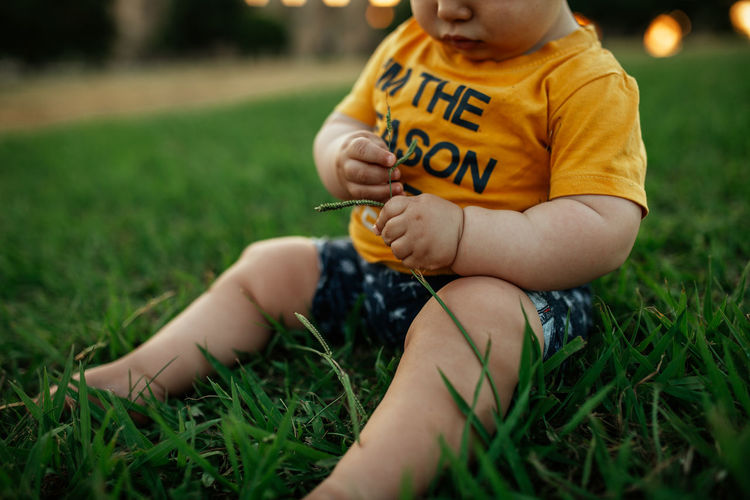 Midsection of boy sitting on field