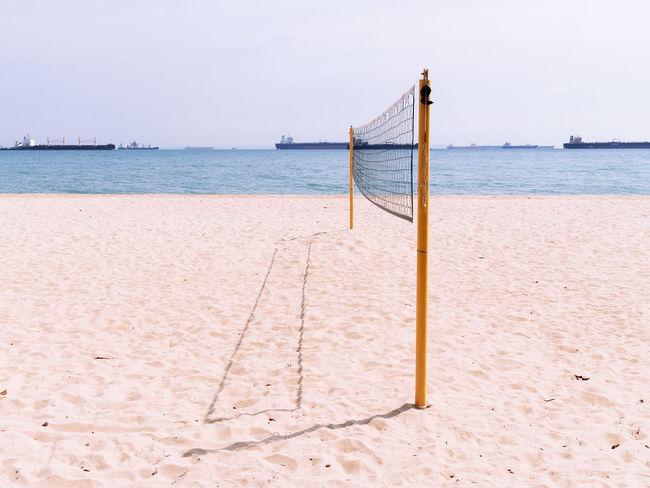 Empty beach volleyball court in bright light condition Beach Sea Water Sand Sky No People Tranquility Outdoors Volleyball Court Net Poles Hot Hot Weather Summer Recreation  Competition Exercise