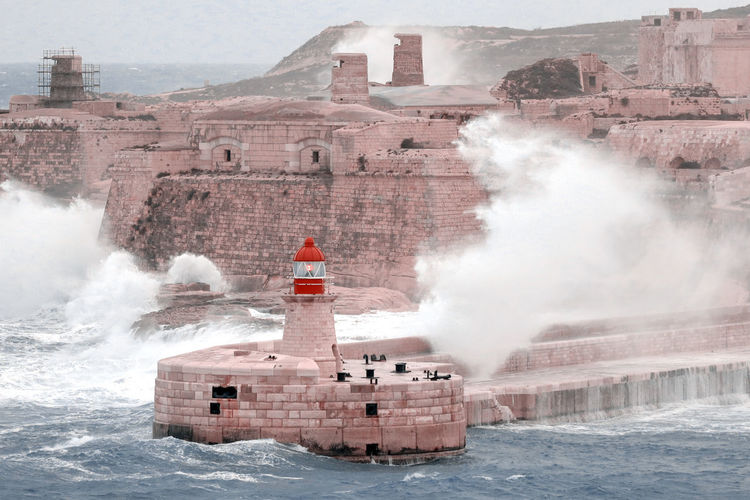 Huge waves crash against the breakwater at the entrance of valletta's grand harbour, malta
