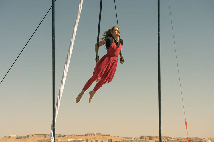 Full length of female aerial dancer dancing while hanging from textile against sky