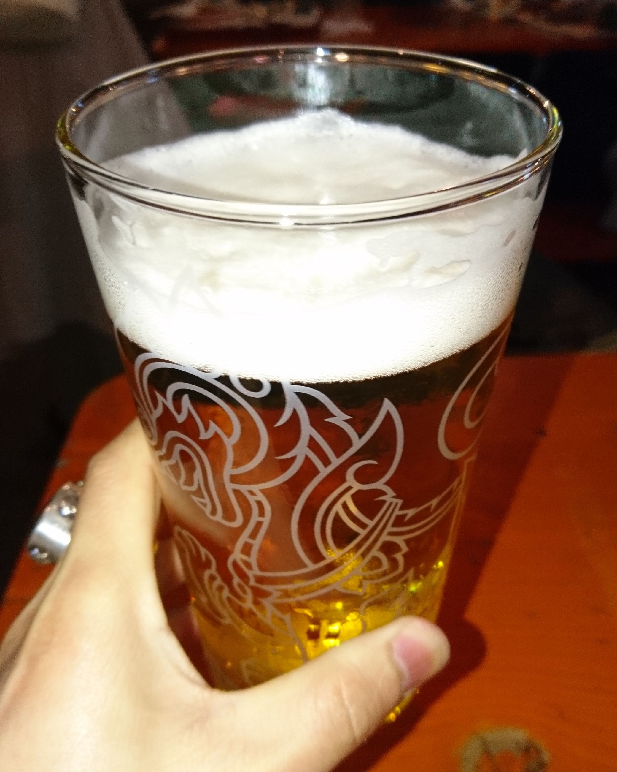 human hand, real people, drink, food and drink, one person, human body part, holding, refreshment, beer glass, drinking glass, personal perspective, freshness, lifestyles, beer, leisure activity, table, close-up, frothy drink, indoors, alcohol, women, food, day