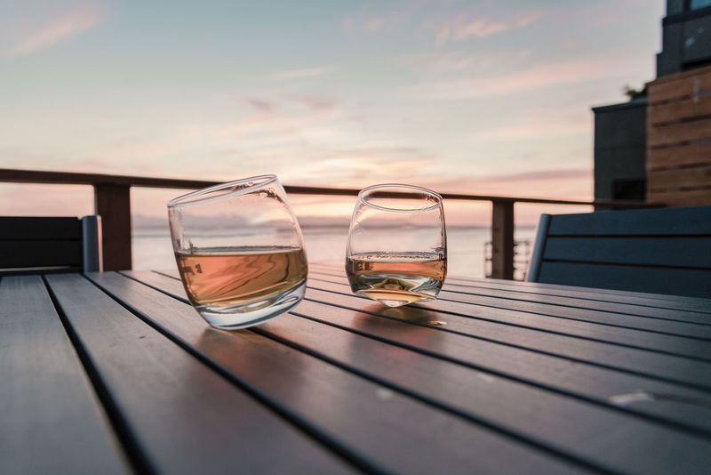 Two tumbler whiskey glasses on outdoor dining table at sunset by the sea. Beach House Copy Space Romantic Al Fresco Alcohol Bourbon Cloud - Sky Drink Focus On Foreground Food And Drink Nature No People Outdoors Rocks Scotch Sea Slats Summer Sunset Table Tequila Tumblers Whiskey