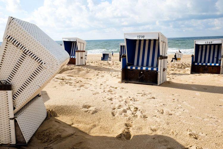 Hooded beach chairs on sand against sea