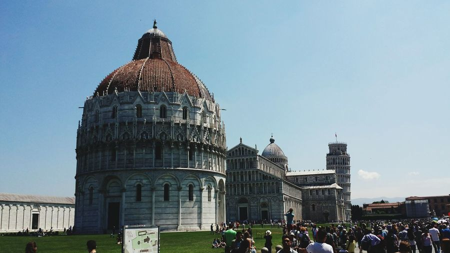 People outside piazza dei miracoli and leaning tower of pisa against clear sky