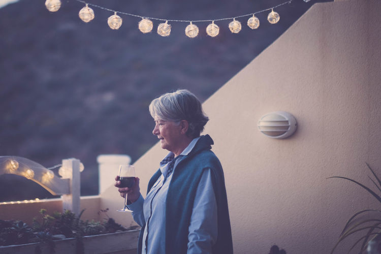 elderly woman drink some wine during an event Gray Hair Plants Positive Moments Thinking Vacations Adult Architecture Casual Clothing Decoration Drink Emotion Focus On Foreground Holding Illuminated Leisure Activity Lifestyles Light Lighting Equipment Mobile Phone One Person Real People Sunset Waist Up Women