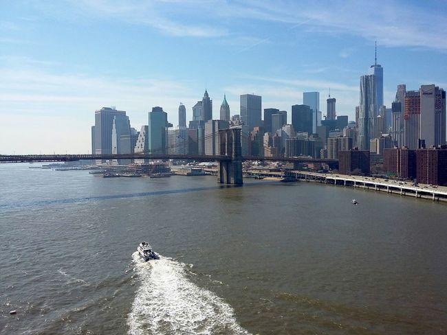 Manhattan from the Manhattan Bridge. · New York City New York ❤ NYC USA Skyline Cityscape Architecture Highrises Urban Landscape Waterfront Boat Boat Wake Bridges Great View Tourist Spot