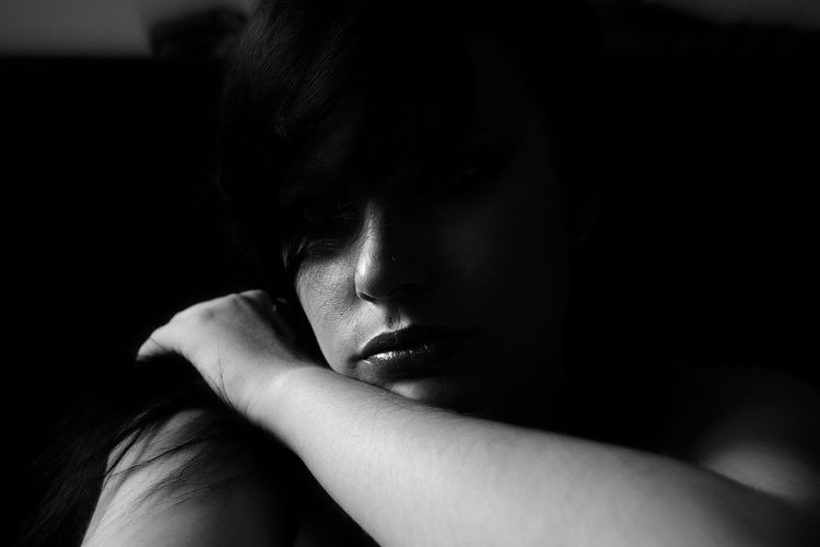 Sad young woman with hand on shoulder at home