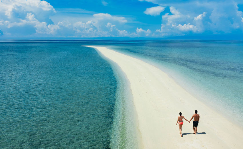 A couple walks along a sandbar in the Philippines. Beach Couple Holding Hands Honeymoon Horizon Over Water Inspiration Marriage  Outdoors People Philippines Romance Romantic Sand Sea Sky Together Together Forever Togetherness Travel Destinations Two People Walking