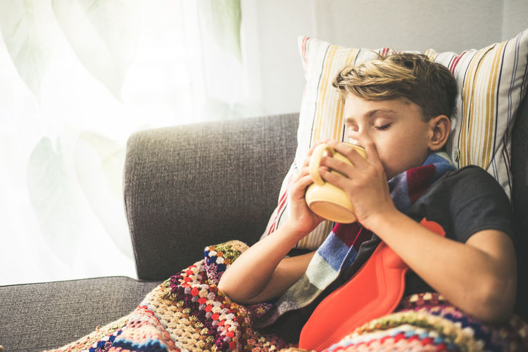 Boy drinking coffee while resting on sofa at home