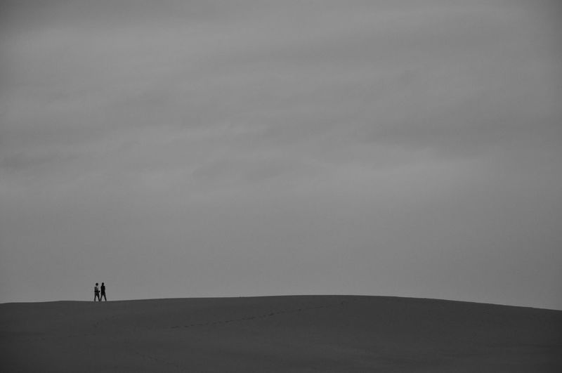 Silhouette People Walking On Landscape Against The Sky