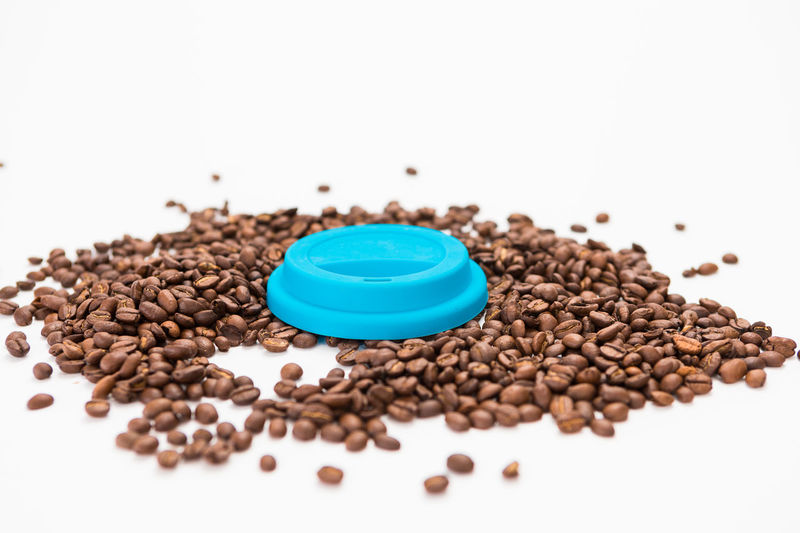 Silicone Coffee Cup Lids On Coffee Beans on White Background White Background Indoors  Studio Shot Food And Drink Brown Still Life Roasted Coffee Bean Large Group Of Objects Food Close-up Freshness Coffee - Drink Coffee Selective Focus No People Copy Space High Angle View Abundance Raw Food Wellbeing Caffeine