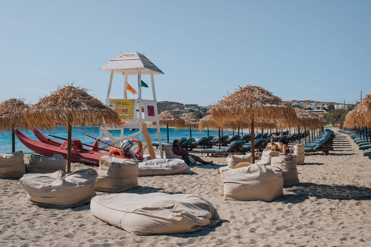 Lounge chairs and parasols on beach against clear sky