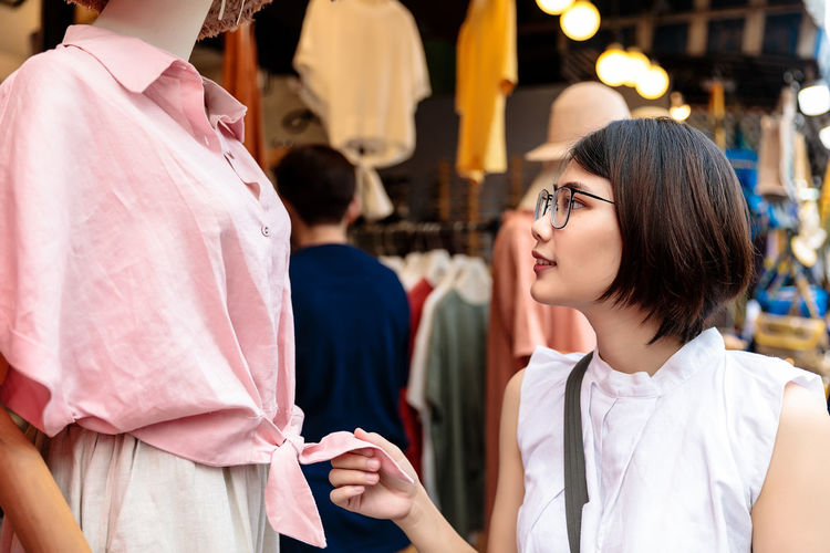 Woman looking at garments in clothing store