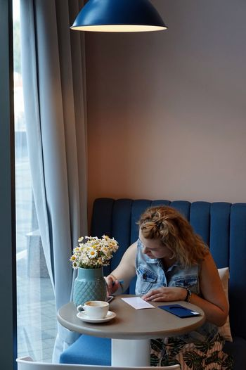 Young woman writing at home