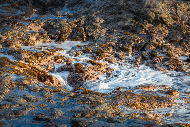 Water of the pacific ocean running across rocks back into a blowhole