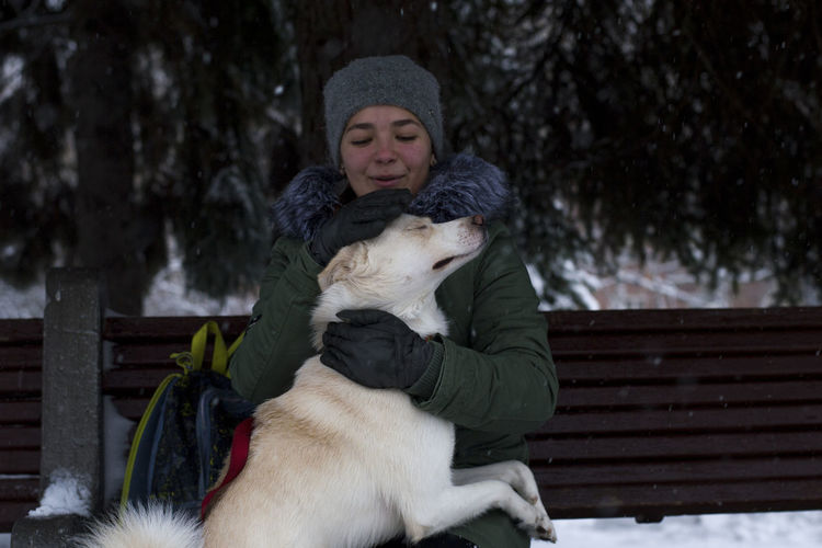 Young Woman Stroking Dog While Sitting On Bench At Park During Winter