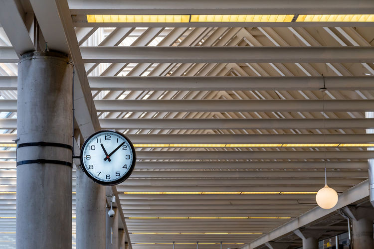 Low angle view of illuminated clock hanging on ceiling in building
