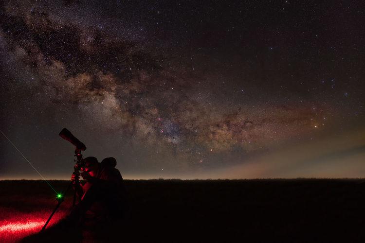 Silhouette of man star gazing at night