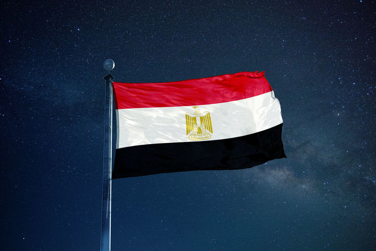 Low angle view of egyptian flag against star field sky