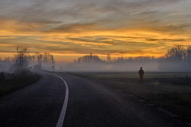 Man standing on road against orange sky
