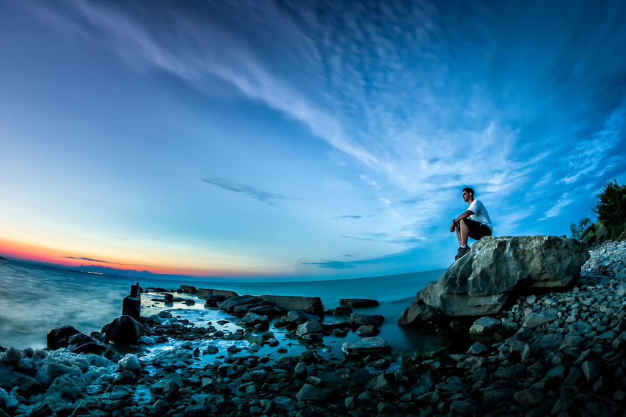 Travel Adventure Beauty In Nature Blue Cloud - Sky Horizon Over Water Lake Leisure Activity Lifestyles Looking Men Nature Outdoors Real People Resting Rock Scenics - Nature Stone Summer Sunrise Sunset Tourism Tranquility Watching Water