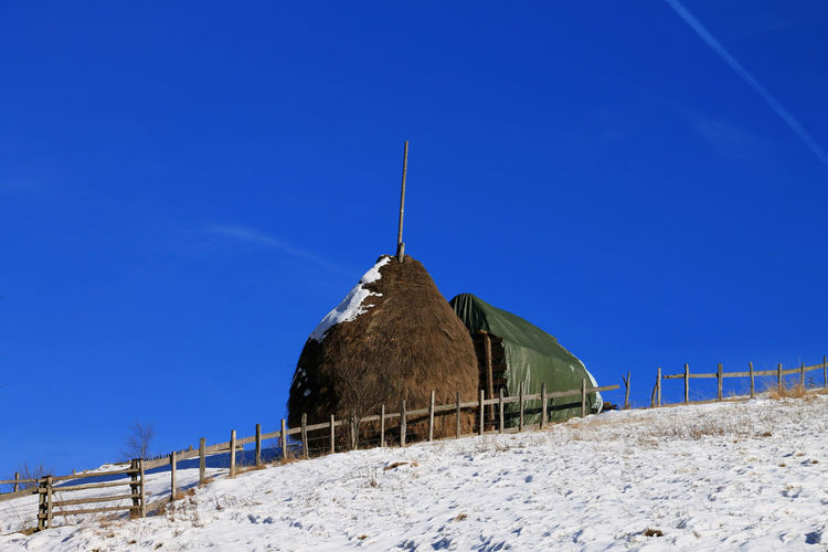 Built structure on field against clear blue sky during winter