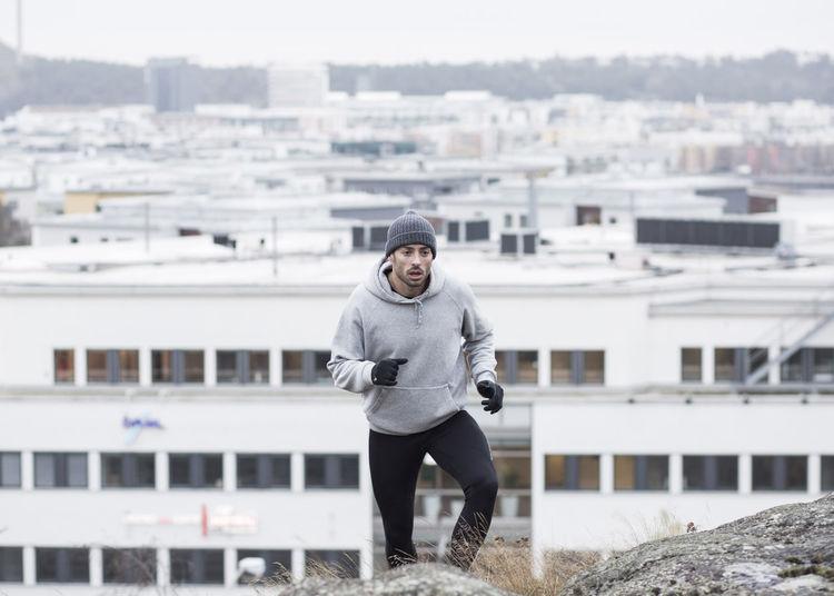 Portrait of smiling man in city against buildings