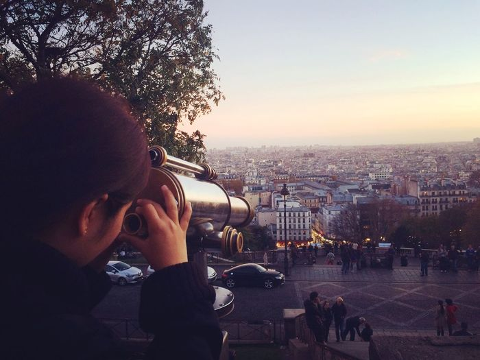 Woman looking at cityscape through coin-operated binoculars during sunset
