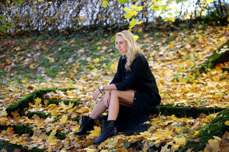 Young woman sitting on autumn leaves