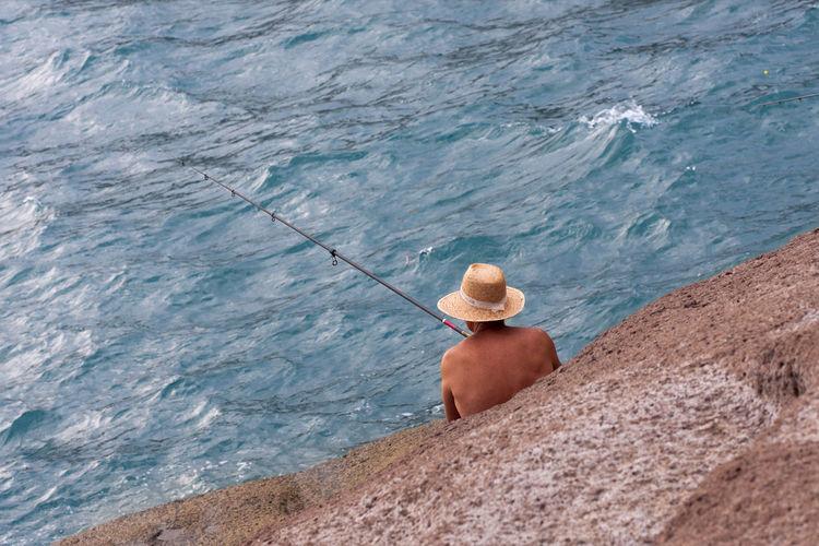 Rear View Of Man Fishing At Seaside