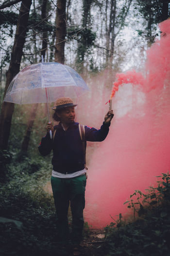 Man With Umbrella And Red Smoke Standing In Forest