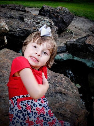 Portrait of cute girl sitting on rock in park