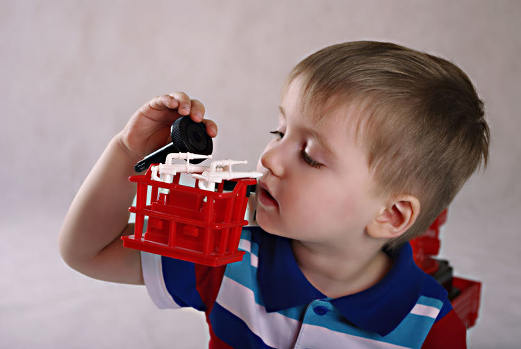 Close-Up Of Cute Boy Playing With Toy