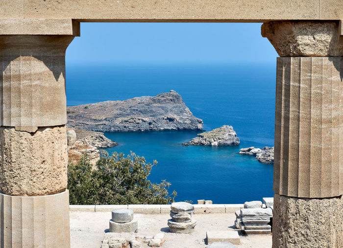 View trough antique columns down to the sea at Lindos Acropolis on Rhodes Island, Greece Lindos Acropolis Acropolis Lindos Architecture Beauty In Nature Built Structure Clear Sky Day Horizon Over Water Lindos Lindos Greece Nature No People Outdoors Scenics Sea Sky Sunlight Tranquility Water An Eye For Travel