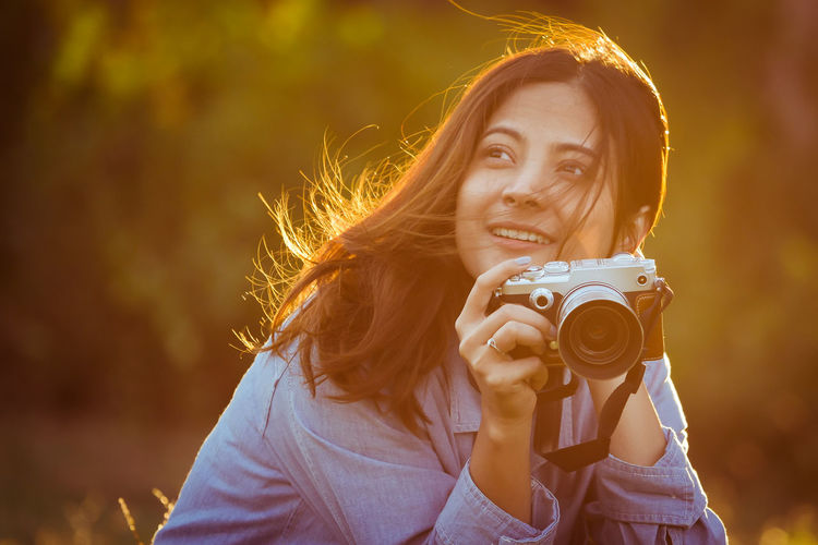 Close-up of smiling young woman holding camera