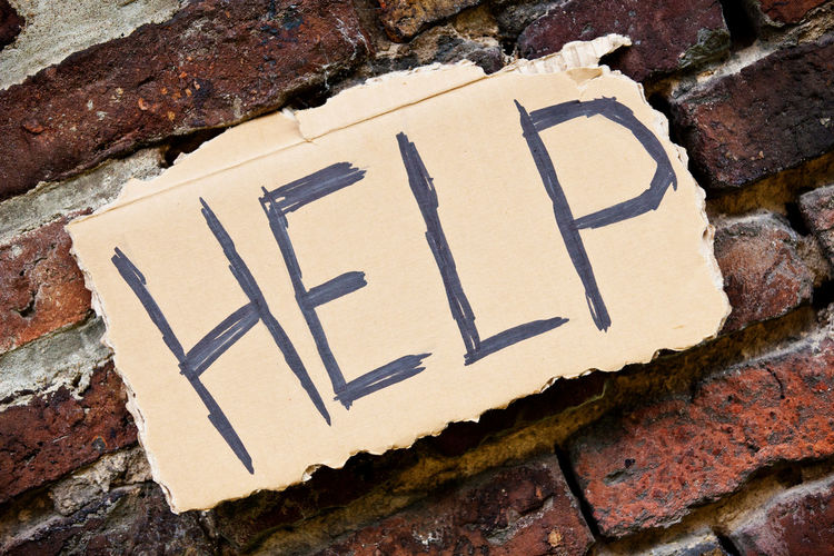 Close-up of help text on brick wall