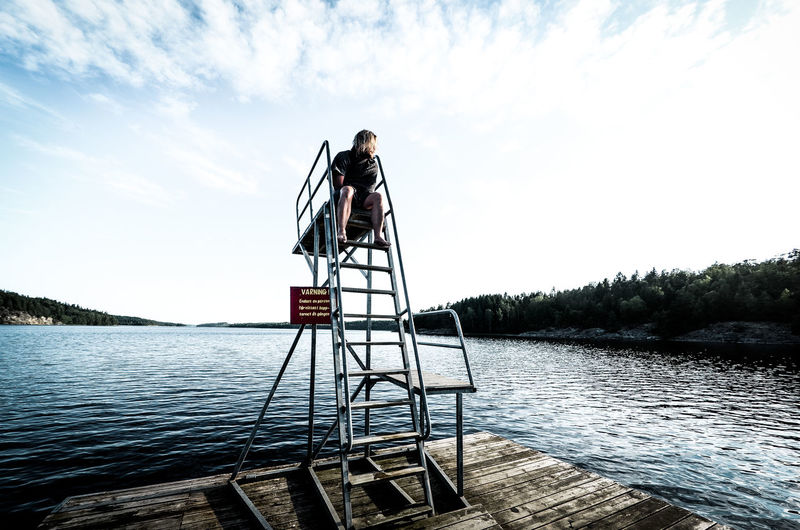 Woman sitting on diving platform by lake against sky