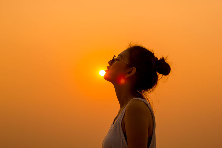 Side view of young woman against sky during sunset