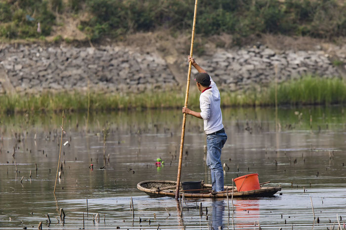 Man on a small rowboat with Mountains in the background Vietnam Activity Casual Clothing Day Fisherman Fishing Fishing Industry Fishing Rod Full Length Holding Lake Men Nature One Person Outdoors Rod Standing Vietnamese Man Water