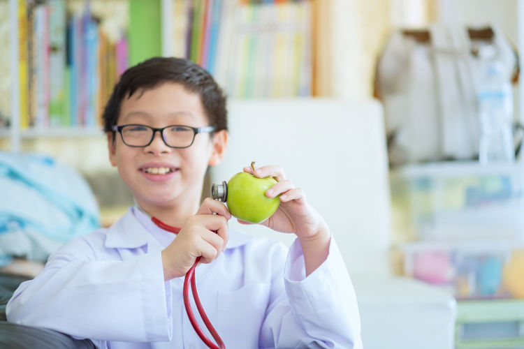 close up of boy hands with green apple, Little cute boy future doctor dressed white medical apron with stethoscope and green apple Boys Casual Clothing Child Childhood Emotion Eyeglasses  Focus On Foreground Front View Glasses Holding Innocence Lifestyles Looking At Camera Males  Men One Person Portrait Real People Smiling