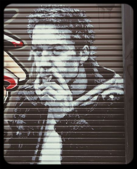 Nils Westergard Stencil on a Rollerdoor of a smoking man Streetart at its best