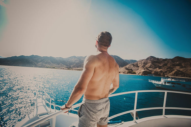 Shirtless Man Standing On Boat In Sea Against Sky