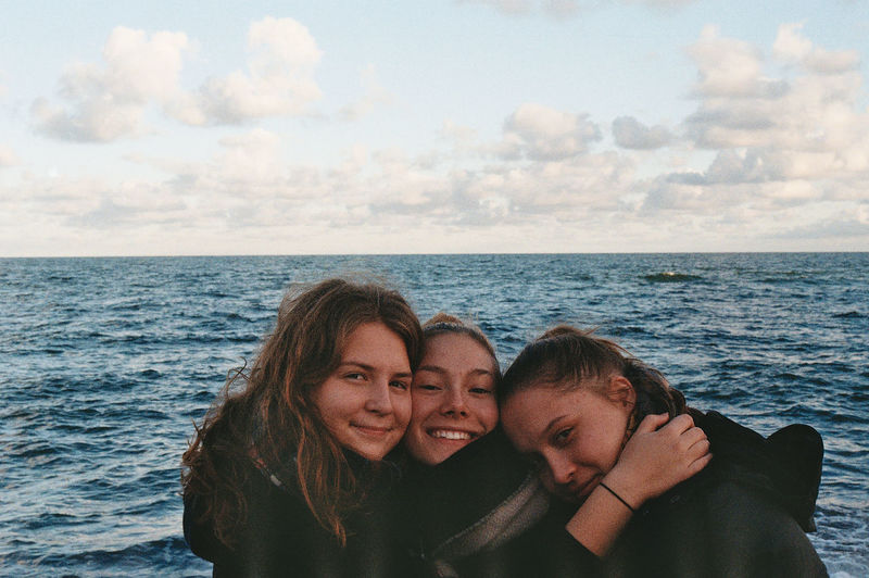 Portrait of smiling women against sea and sky
