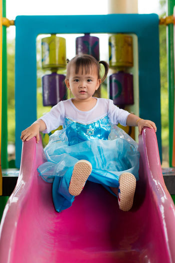Childhood Day Front View Full Length Fun Happiness Leisure Activity Lifestyles One Person Outdoors Playground Playing Real People Sitting Smiling