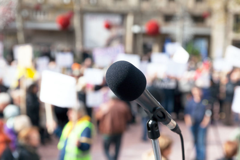 Close-up of microphone against people standing outdoors