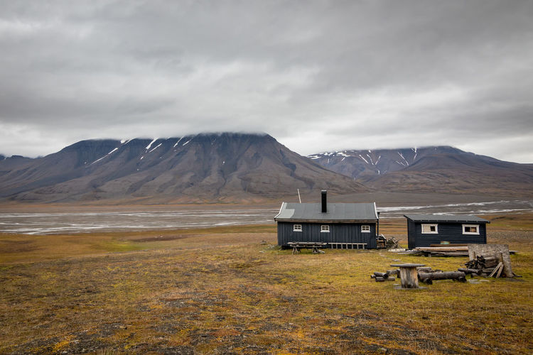 Typical wooden cottange in arctic landscape in svalbard, norway. scenic view of adventdalen