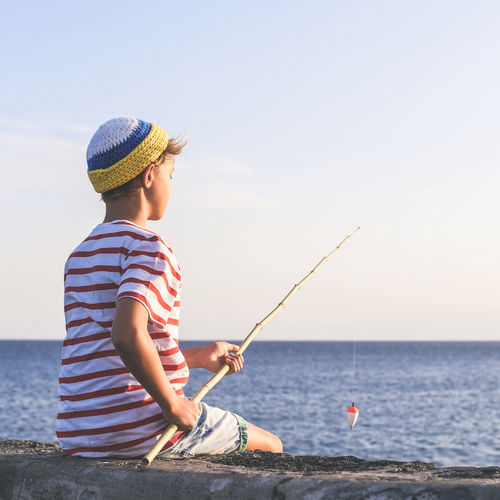 Boy sitting on retaining wall while fishing in sea