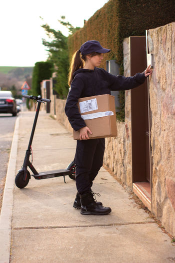 Full length of delivery person holding parcel standing on footpath