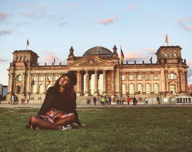 Portrait of young woman sitting against the reichstag
