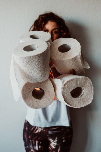 Portrait of woman holding toilet paper rolls